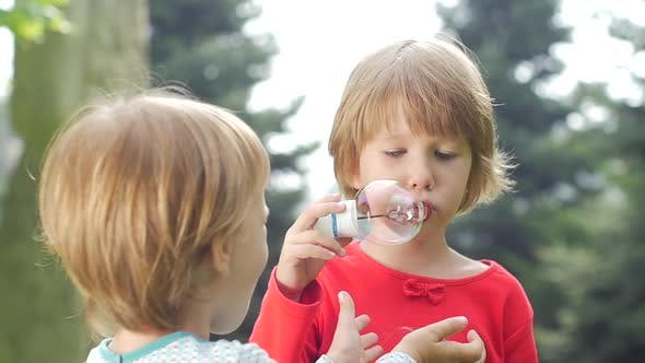 Thumbnail for Two Girls Are Blowing Bubbles in the Park, Slow Motion. Close Up