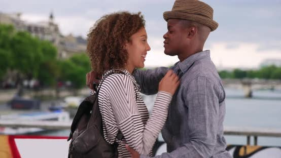 Thumbnail for Happy millennial couple stand on Paris bridge smiling and being affectionate