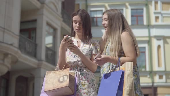 Cover Image for Two Adorable Happy Girlfriends After Shopping with Shopping Bags Texting on the Cellphone in Front