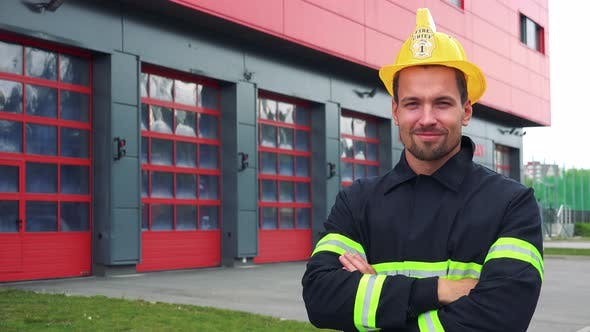 Thumbnail for A Young Firefighter Smiles at the Camera and Folds His Hands Across His Chest - a Fire Station
