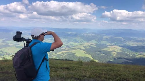 A man photographs a mountain landscape while hiking in the mountains.