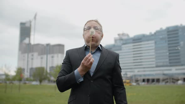 Thumbnail for Funny Plump Man in Suit and Glasses Blows on Dandelion Outside the Office, Adult Manager in Street
