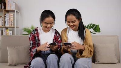 Asian twin girls watching smartphone