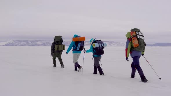 Thumbnail for Four Young People Go Hiking in the Snowy Desert.