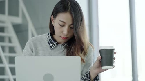 Young Asian female manager using portable computer device and drinking coffee cup at office