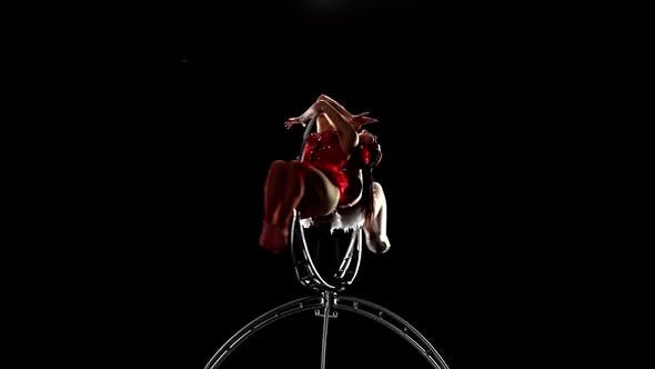 Thumbnail for Aerial Gymnasts Performs a Trick on the Hoop Metal Construction. Black Background. Slow Motion