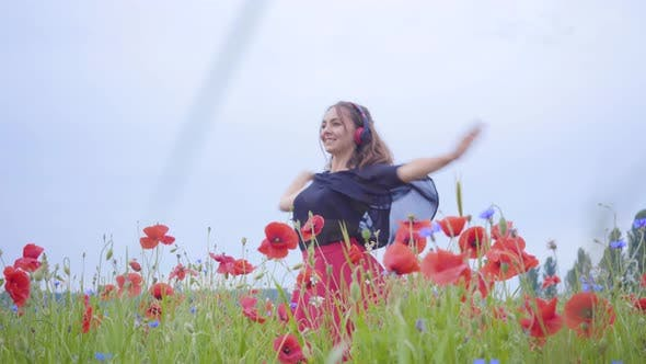 Cover Image for Adorable Young Woman Wearing Headphones Listening To Music and Dancing in a Poppy Field Smiling