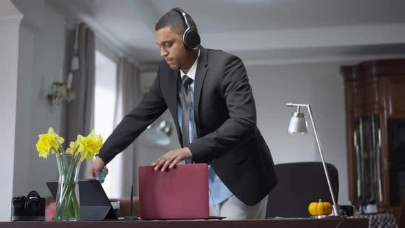 Junger afroamerikanischer Mann reinigt den Arbeitsplatz zu Hause drinnen