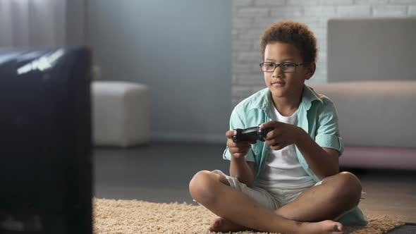 Cover Image for Afro-American Schoolboy Spending His Free Time Playing Games on Console, Leisure