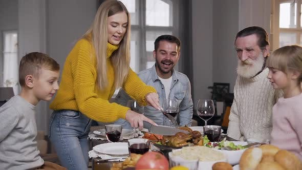 Thumbnail for Smiling Woman in Knitted Sweater Carving Roast Turkey During Family Festive Dinner