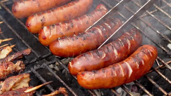 Hot Tasty Grilled Sausages Frying on Smoking Barbecue