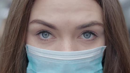 Thumbnail for Close-up of Grey Eyes of Young Woman in Protective Mask Looking at Camera. Portrait of Brunette