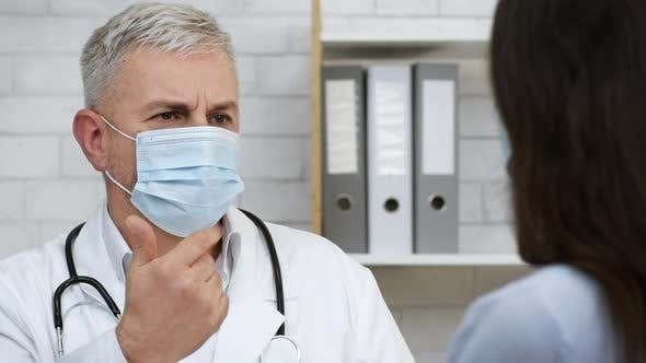 Doctor Talking Consulting Sick Female Patient Suggesting Treatment In Office
