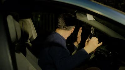 Driver in Sweater Raises Hands with Empty Alcohol Bottle
