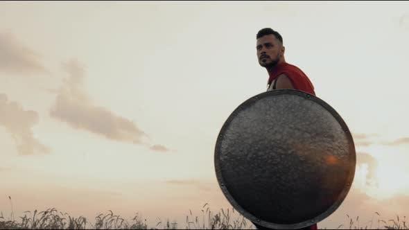 Spartan with Shield Walking in Dry Field.