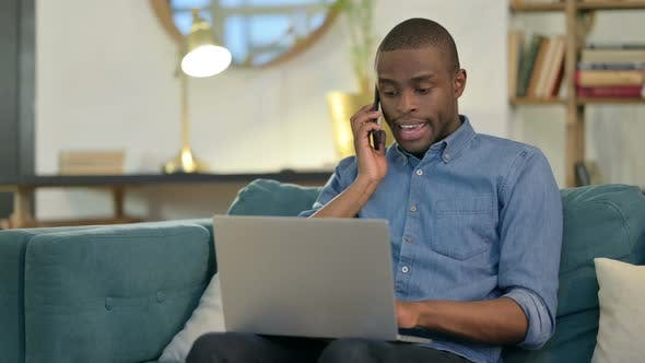 Cover Image for Young African Man with Laptop Talking on Smartphone on Sofa