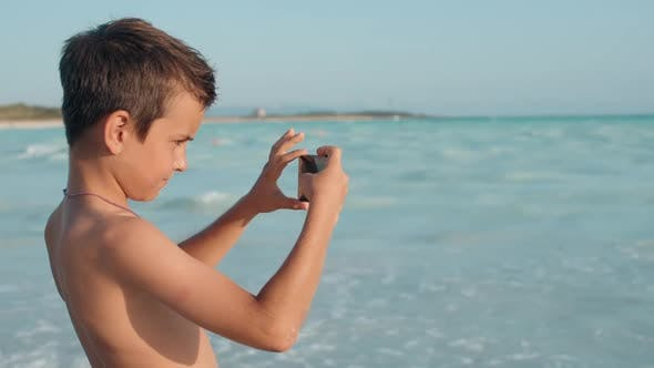 Boy Making Pictures on Cellphone at Seaside