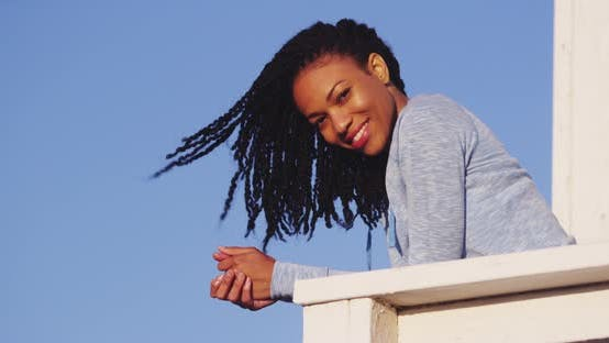 Thumbnail for Happy black woman leaning on rail smiling