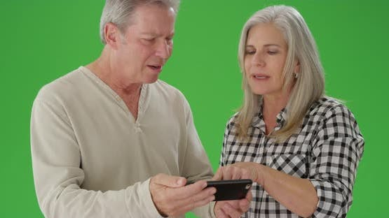 Two mid aged white people looking at a cellphone