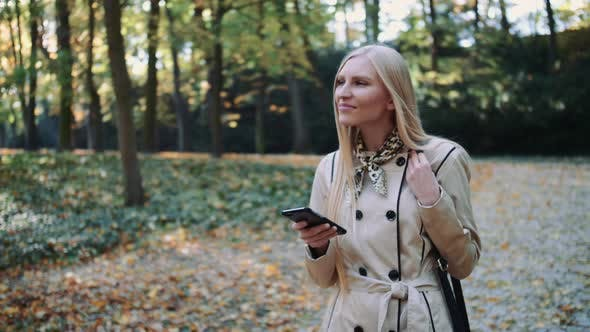 Thumbnail for Young Girl Walking in Autumn Park and Texting a Message on a Mobile Phone