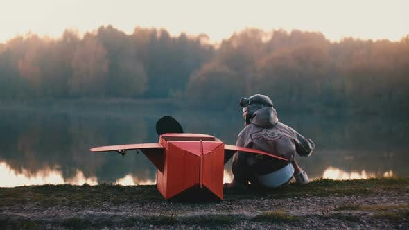 Thumbnail for Back View Little Boy in Old Pilot Costume Sitting at Amazing Forest Lake with Fun Red Cardboard