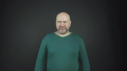 Bald Man with Grey Stubble Performs Emotions of Anger