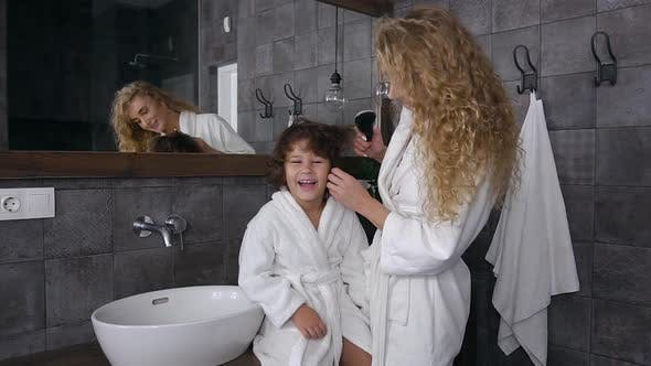 Cover Image for Blond Mother Having Fun Together with Her Smiling Little Son while Combing His Hair
