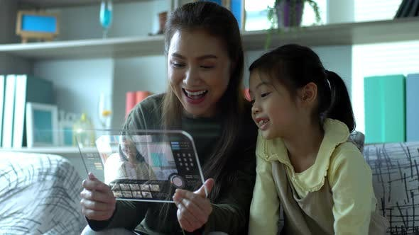 Asian Mother And Daughter Playing With An advance Tablet Mock Up 01