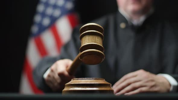 Thumbnail for Judge's Hand With Wooden Gavel Hammering Against American Flag In United States Court