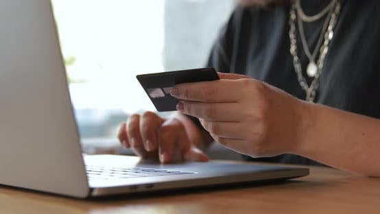 Girl using laptop for online internet shopping checkout with credit card payment.