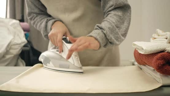 Close-up of Female Caucasian Hands Ironing Laundry Indoors. Unrecognizable Young Woman Doing