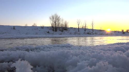 Steam Comes Out of Water and Stream Flowing Under Frozen Ice Sheets in Sunset Morning Time