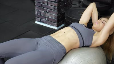 young beautiful woman doing fitness exercise abdominal training at fitness club