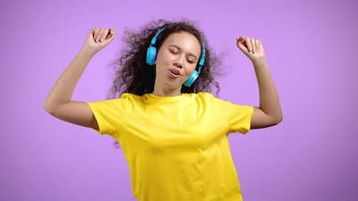 Young Woman Listening To Music Dancing with Headphones on Violet Studio Background