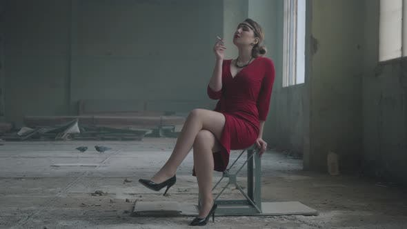 Thumbnail for Portrait Elegant Woman in Red Elegant Dress Sitting on the Chair in the Abandoned Building Smoking