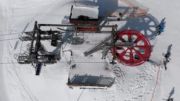 Thumbnail for Luftaufsicht des Skilifts für den Transport Skifahrer auf der verschneiten Skipiste. Drohne fliegt über Stuhl