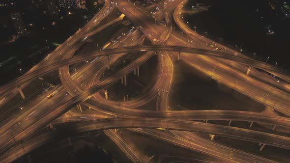 Illuminated Complex Road Junction and Cars Traffic at Night. Drone Is Orbiting Around. Aerial View