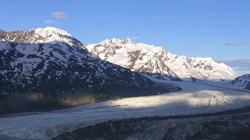Luftaufnahme von Gletscher und See mit verschneiten Bergen, Alaska