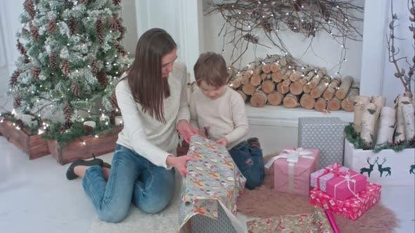 Thumbnail for Niedlicher kleiner Junge hilft seiner Mutter, Papier zum Verpacken von Weihnachtsgeschenken zu schneiden