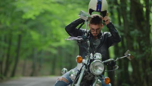 Thumbnail for Young man gets on motorcycle and rides away