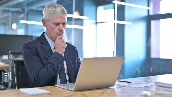 Thumbnail for Middle Aged Businessman Thinking and Working on Laptop