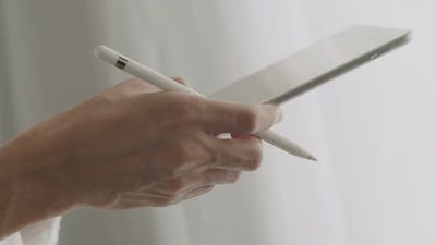 Close-up businessman signing a digital contract on a tablet.