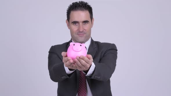 Cover Image for Happy Handsome Businessman Giving Piggy Bank
