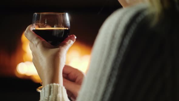 Cover Image for Hand with A Glass of Wine of A Woman Who Is Relaxing by The Fireplace