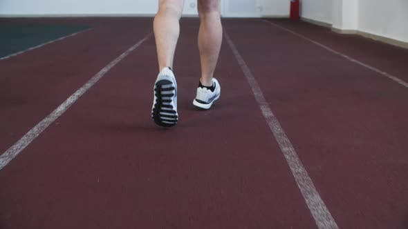 Close Up Jogger Legs in Sports Sneakers Running on Treadmill in Gym Back View