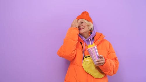 Smiling Mature Model Posing on a Lilac Background in Bright Winter Clothes, Good Mood