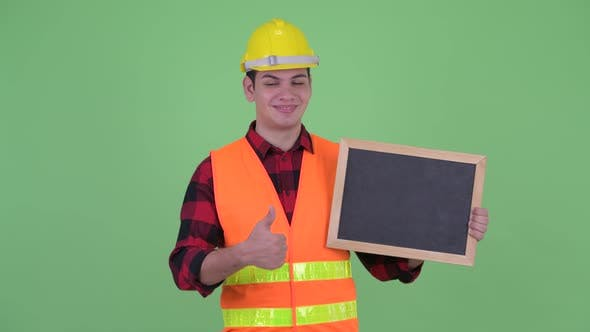 Thumbnail for Happy Young Multi Ethnic Man Construction Worker Holding Blackboard and Giving Thumbs Up