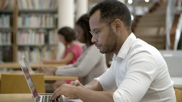 Thumbnail for Side View of Focused Young Man Using Laptop at Library