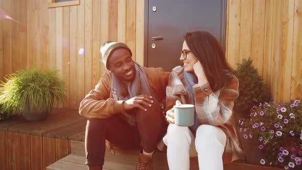 Glückliches multiethnisches Paar beim Chatten auf der Veranda