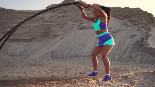 Thumbnail for Close-up of a Girl with a Rope Conducts Outdoor Training on the Sandy Ground Near the Beach